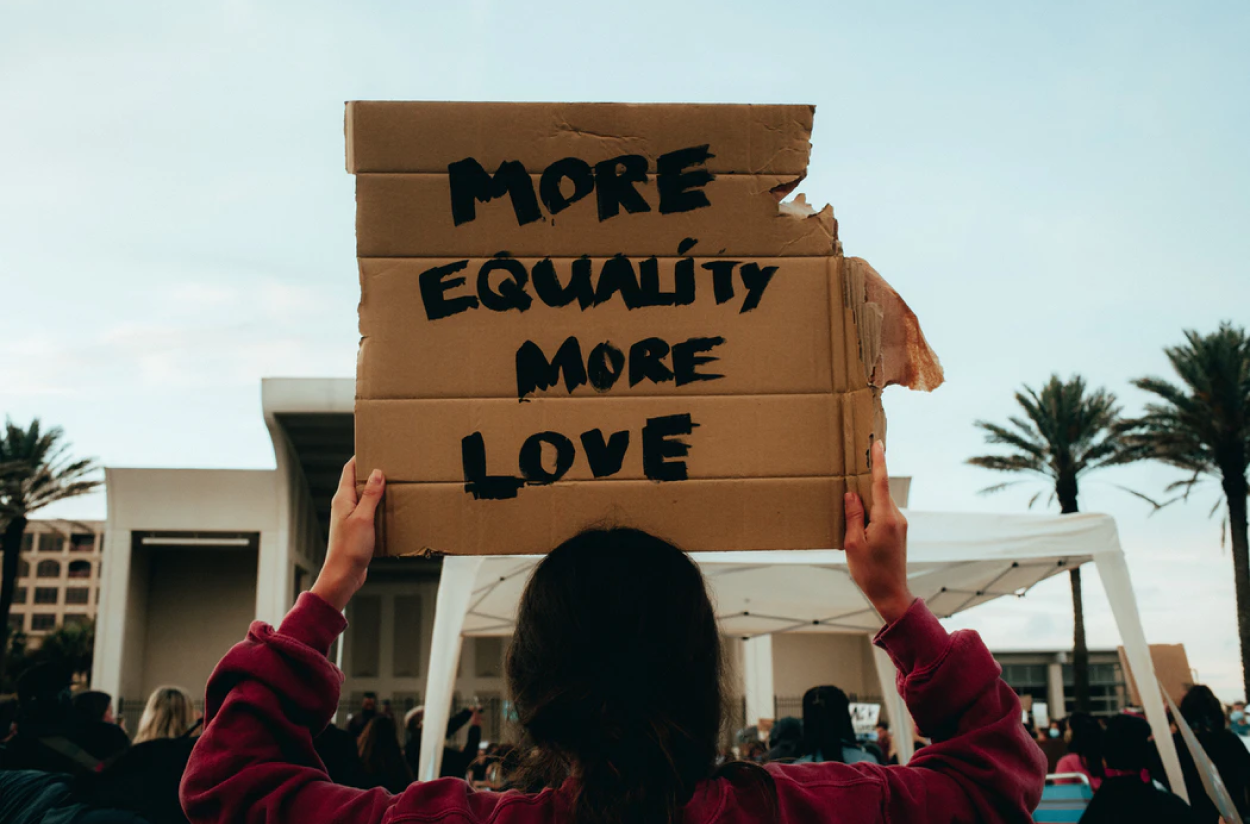 women holding up sign saying 'more equality more love'