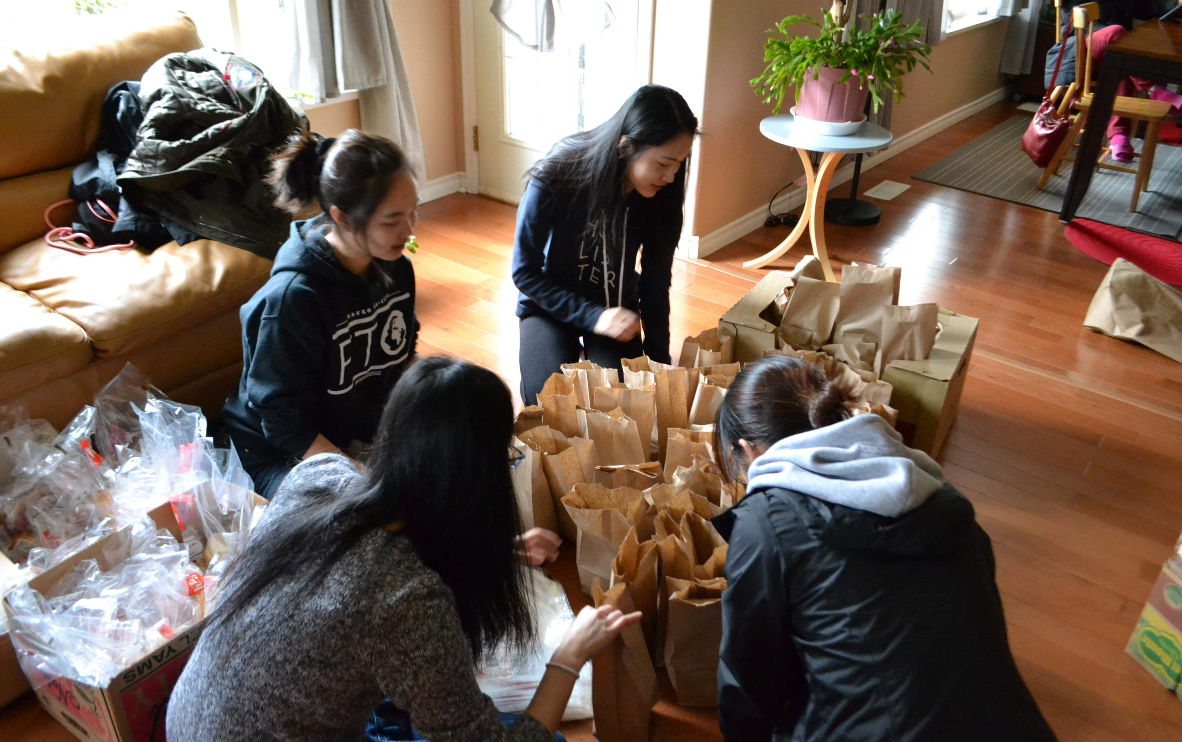 4 people organizing bags of food