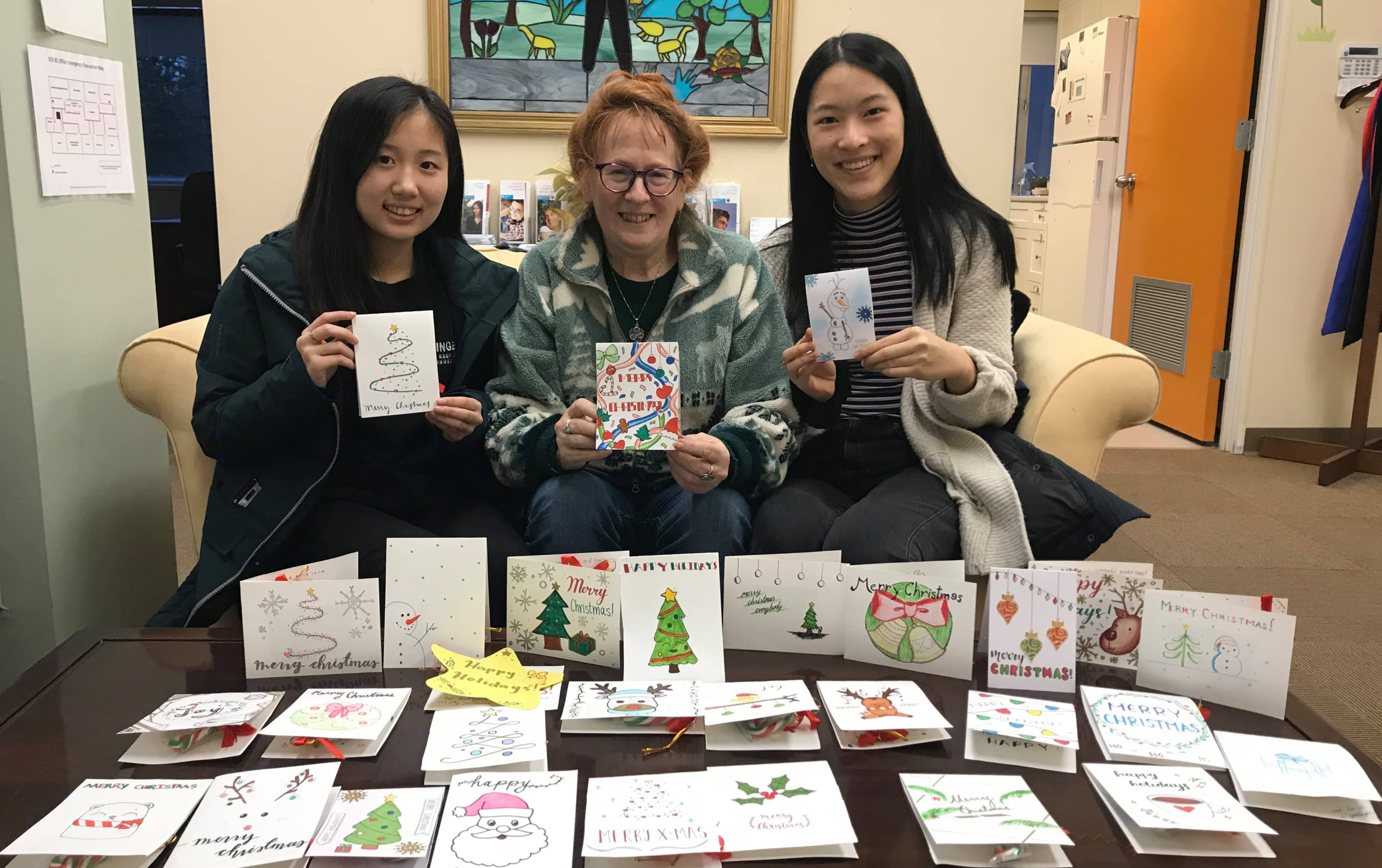 3 people holding up christmas cards